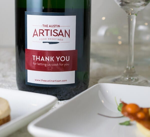 a bottle of wine of which the label reads the Austin Artisan Thank You
