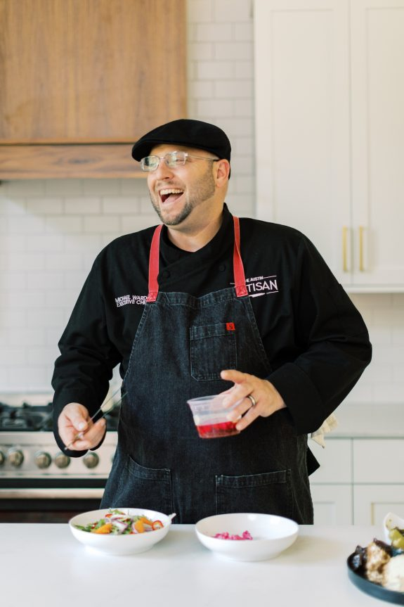 Michael Wards, a Personal Chef in Austin Laughing while Preparing Salad in Home Kitchen