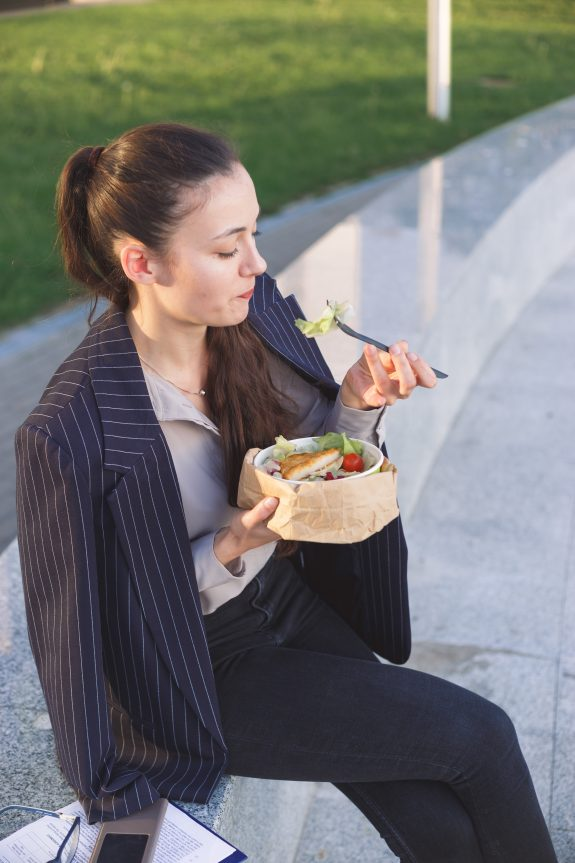 Image description: Young business woman eating lunch outside.