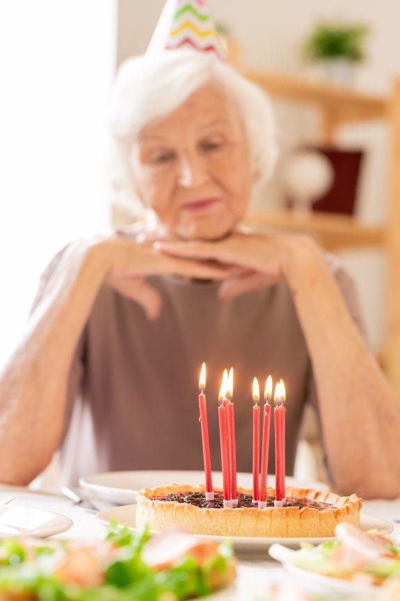 Senior woman eats birthday cake alone.