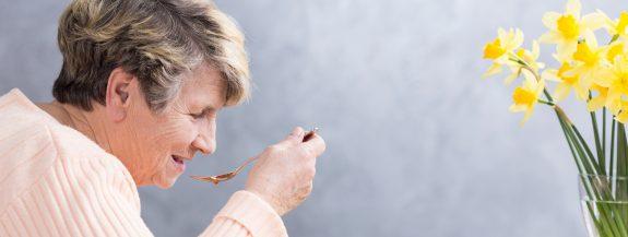 Senior woman eats delicious food.
