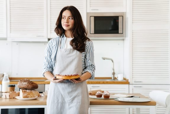 Woman stands in kitchen holding a pie.