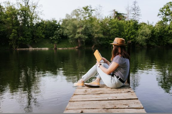 Woman reads an inspiring book on a dock by a river.