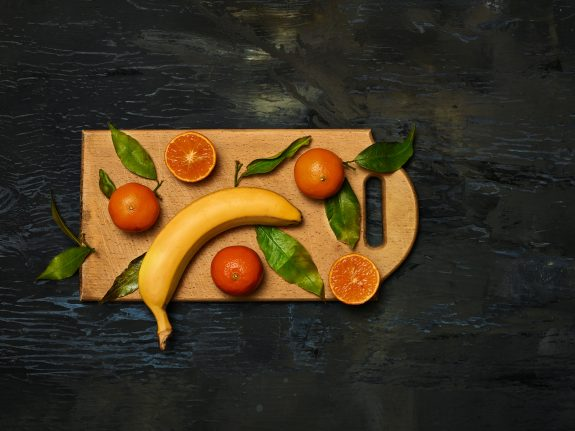 Delicious array of seasonal fruits including oranges and banana.