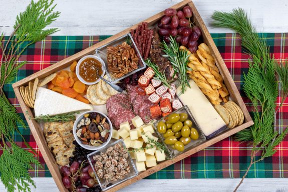 This charcuterie board features pecans, toasted bread, and dried fruits.