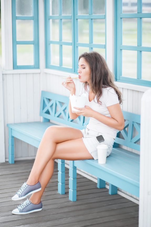 Woman sits on a bench and eats a snack.