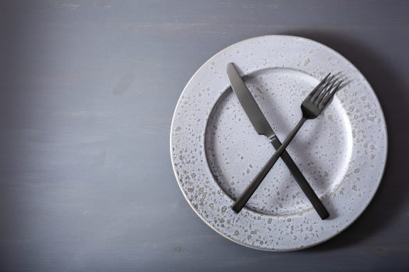 Knife and fork sit on an empty plate.