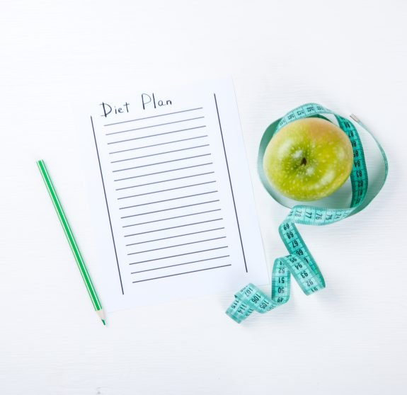 Diet plan journal page sits next to apple and measuring tape.