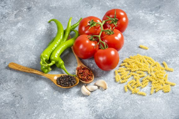 Tomatoes, peppers, and macaroni sit on a counter.