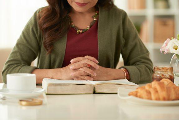Woman reads a book while taking a snack break.