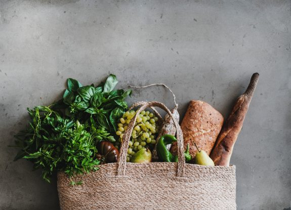 Healthy eats pour out of woven bag.