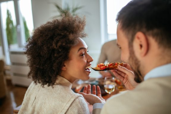 Man feeds dinner items to woman.