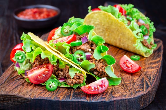 Three hard-shelled ground beef tacos sit on a wooden slab.