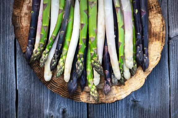 White, purple, and green asparagus sit on a wood plate.