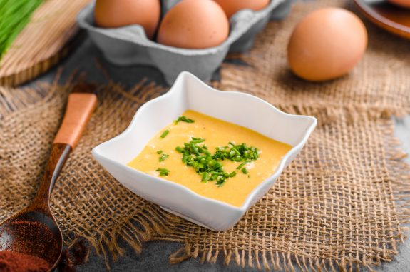 Dish of Hollandaise sauce sits next to a package of eggs.