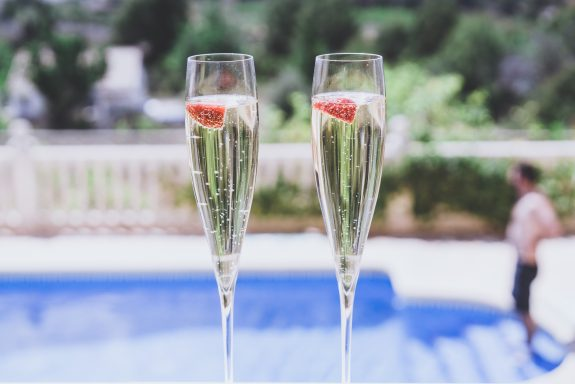 Two champagne glasses with strawberries.