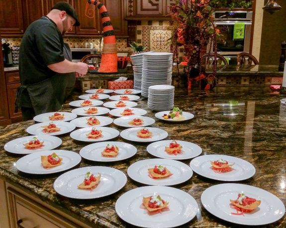 An Austin Artisan chef prepares a catered meal for a themed private dinner party with orange and autumnal festive colors.