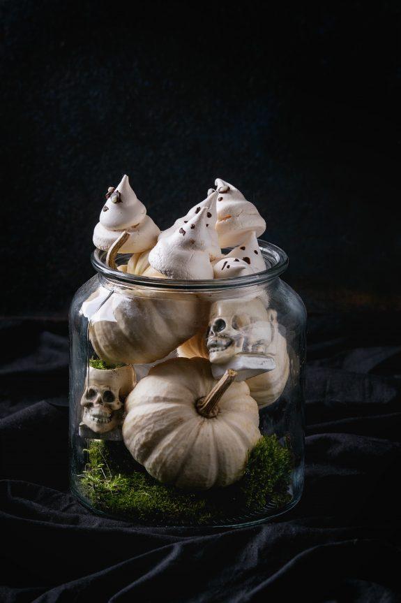 Glass jar contains candies and sugar pumpkins, and skulls.