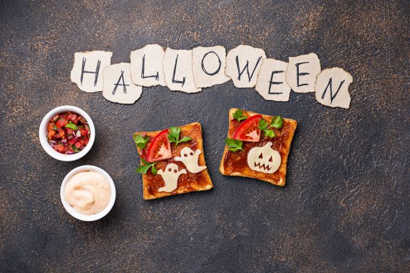 Sandwich toasts with cheese cut in shapes of ghosts and pumpkins.